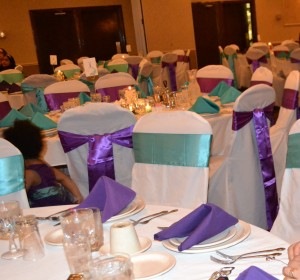 Banquet chair covers with turquoise and purple sashes